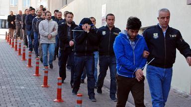 Man sieht eine lange Reihe von Mernschen. Je ein Polizist hat zu seiner linken einen Häftling.