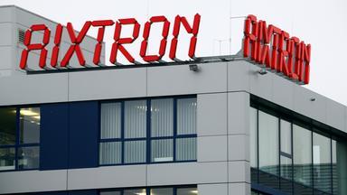 Logo des Chipherstellers Aixtron in roter Leuchtschrift auf einem Firmengebäude.