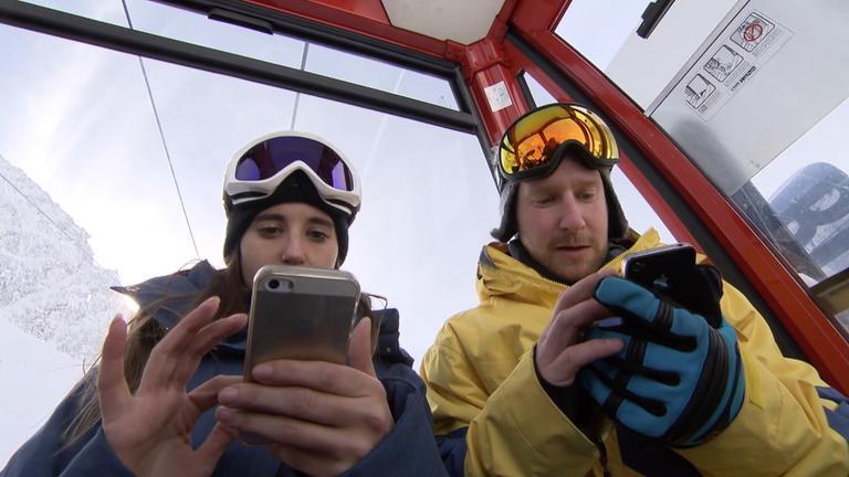 Skifahrer in Gondel schauen auf ihre Handys