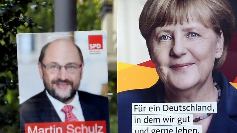 Zwei Wahlplakate, im Vordergrund ein CDU-Plakat von Angela Merkel, dahinter ein SPD-Plakat von Martin Schulz