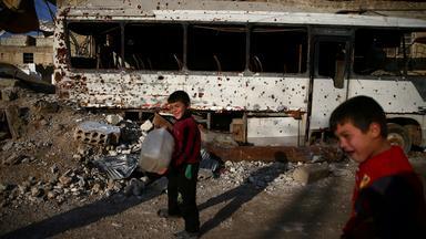 Zwei Jungen stehen mit Wasserkanistern vor Trümmern und einem ausgebrannten Bus in Damaskus