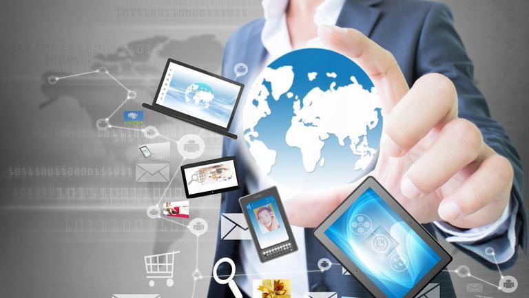 Symbolbild: Hand hält Globus, der von PC, Laptop, Tablet, Mobiltelefon umschwirrt wird.