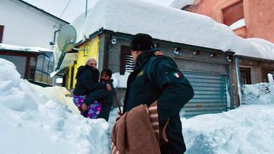 Zwei Männer des italienischen Zivilschutzes tragen eine Frau durch den Schnee
